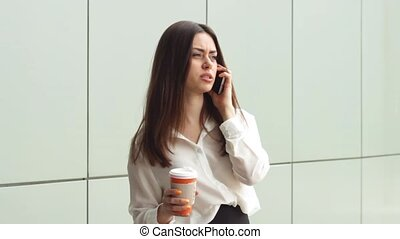 Young businesswoman with hot drink using smartphone - Woman...