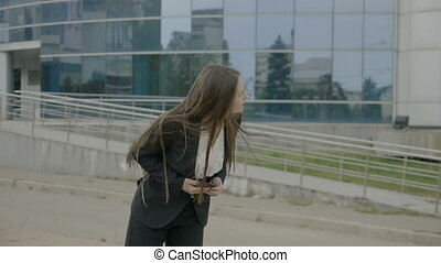 Young businesswoman with long hair wearing formal outfit...