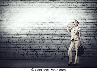 Young businesswoman with suitcase using spray