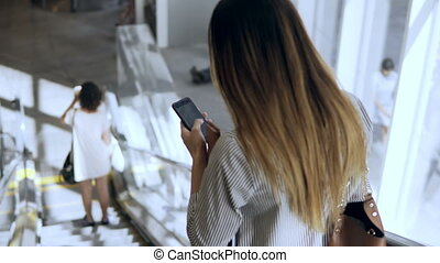 Young businesswoman working in modern office building. Busy female going down on escalator and using the smartphone.