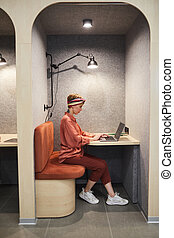 Full length side view portrait of tattooed young woman using laptop while working in cafe booth at office, copy space