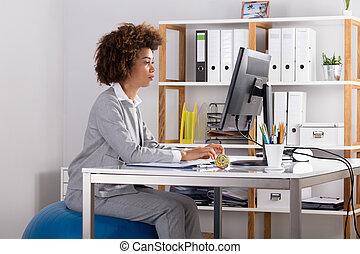 Young Businesswoman Working On Computer At Workplace