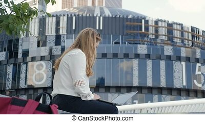 Young businesswoman working on laptop in city park business center