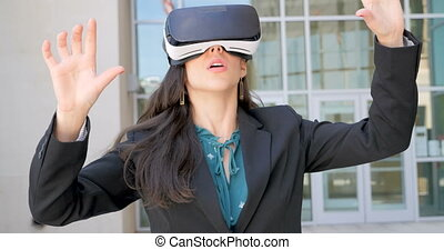 Young businesswoman working with VR headset experiencing virtual reality outside