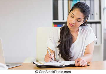 Young businesswoman writing in diary