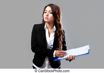 Young businesswoman writing on a clipboard while thinking