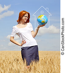 Young Businesswomen in white keeping globe in hand at wheat field. Globe abstract hose frame.