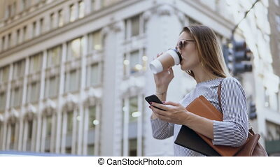 Young busy businesswoman in sunglasses holding the...