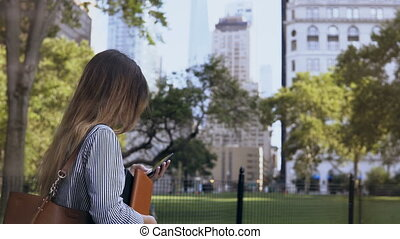 Young busy businesswoman walking to the work, holding the documents and using smartphone in New York, America.