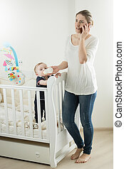 Young busy woman talking by phone while feeding her baby son with milk