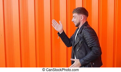 Young caicasian cheerful man moves like a robot on an orange background, close-up, slo-mo
