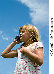 Young girl talking on cell phone with sky background