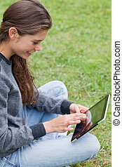 Young calm adult sitting cross-legged on the grass in a park while using her tablet pc