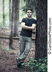 Young calm man in forest.