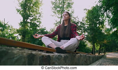 Young calm student girl relaxing, meditating at green park....