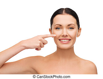 young calm woman pointing to her cheek - health, spa and...