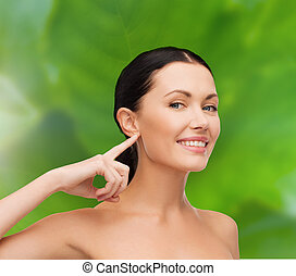 young calm woman pointing to her ear