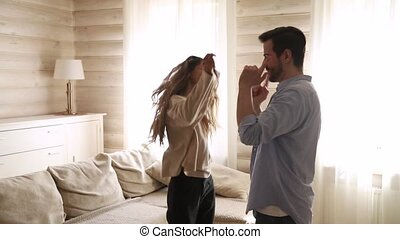 Young carefree active couple dance in living room at home