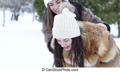 Young carefree girls playing in the winter park. Slowly