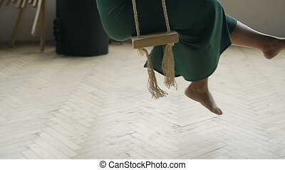 Young carefree pregancy woman swinging on a wooden swing