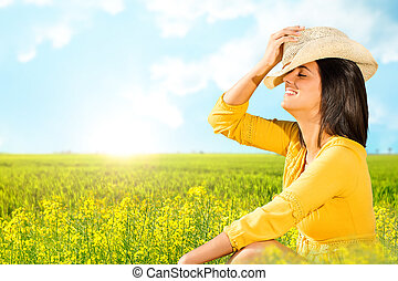 Young carefree woman sitting in green field.