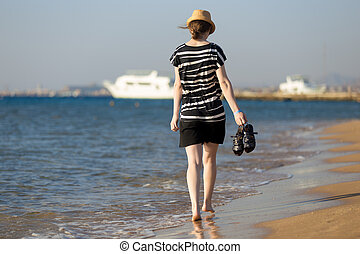 Young carefree woman walking through the surf