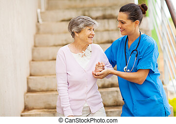 young caregiver helping senior woman