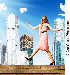 Young careless woman walking on skyscrapers background.