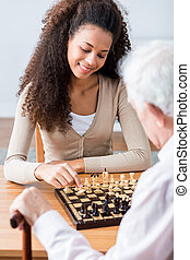 Young carer playing chess with older man - Young pretty...