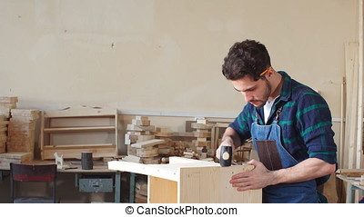 Young Carpenter Hammering a Nail Into Wooden Board. - Young...