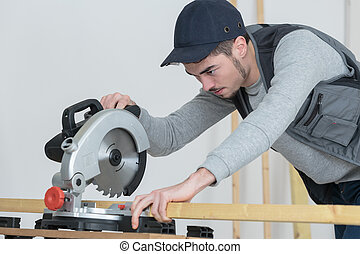 young carpenter using circular saw for wood inside warehouse