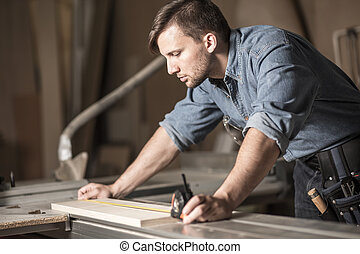 Young carpenter using measuring tape