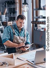 Young carpenter working using laptop