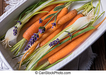 Young carrots and spring onions prepared for baking