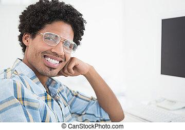 Young casual businessman smiling at camera