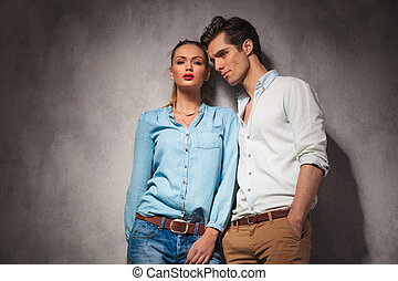 young casual couple standing close to each other