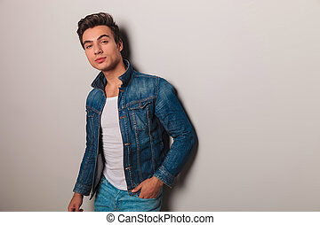 man in jeans jacket leaning on grey wall - young casual man...