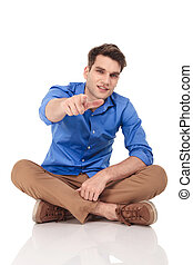 Young casual man pointing his finger at the camera.