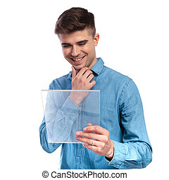 young casual man reading on a transparent futuristic ebook tablet