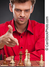 Young casual man sitting over chess. man pointing at chess pieces on board
