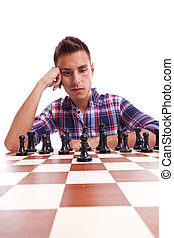 Young casual man thinking in front of the chessboard