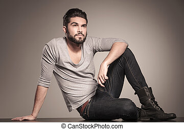 young casual man with beard looks up
