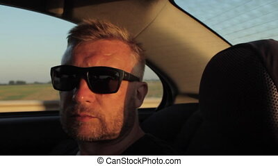 Young casual man with beard portrait sitting on the backseat of car. Urban male hipster in his 30s. Sunset