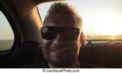 Young casual man with beard portrait sitting on the backseat of car. Urban male hipster in his 30s. Handsome young beared man smiling happy outside looking at camera. Sunset