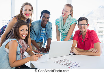 Young casual people using laptop in office - Group portrait...