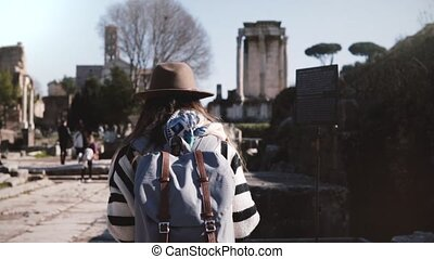 Young casual relaxed female tourist with backpack in stylish clothes walking at the Rome Forum enjoying the scenery.