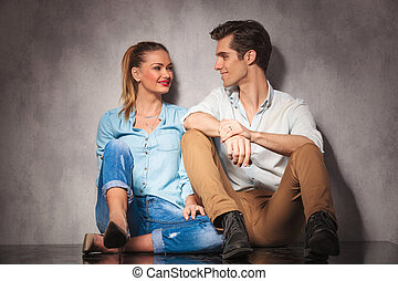 young casual seated couple laughing at each other