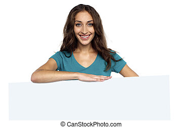 Young casual woman behind blank ad board