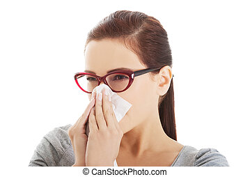 Young casual woman blowing her nose.