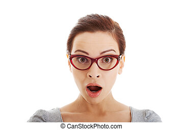 Young casual woman in eyeglasses expresses shock. Isolated...